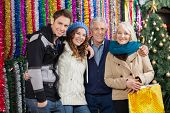 Portrait of happy family standing together against tinsels at Christmas store