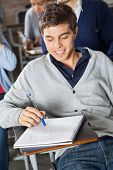 Young male student looking at exam paper in classroom