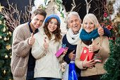 Portrait of happy family with Christmas presents and shopping bags gesturing thumbs up in store