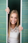 stock photo of movable  - Playful young female student with a mischievous smile peeking out between two movable blackboards - JPG