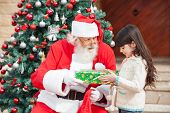 stock photo of nicholas  - Side view of girl taking gift from Santa Claus against Christmas tree - JPG