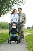 Happy Male And Female Parents Walking With Their Child In Baby Carriage