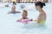 A mother and two daughters are swimming in a public pool