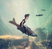 a pretty woman riding a fish under the water of an ocean or sea