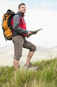 Handsome hiker with rucksack walking uphill holding a map in the countryside