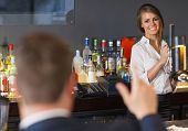 Handsome man ordering a drink from gorgeous waitress in a classy bar
