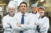 Restaurant manager standing in front of team of chefs smiling at camera