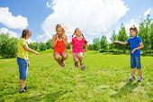 stock photo of skipping rope  - Two girls jumping over the rope with boys rotating the rope - JPG