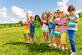 stock photo of sms  - Large group of busy kids boys and girls looking at their phones texting sms and playing staying outside in the field on bright sunny summer day - JPG