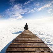 Man In Black Sit On Old Wooden Pier. Winter Coast Of Frozen Baltic Sea