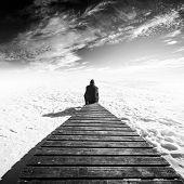 Man Sit On Old Wooden Pier. Winter Coast Of Frozen Baltic Sea