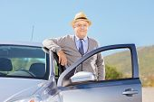 Smiling mature gentleman with hat posing next to his car on an open road