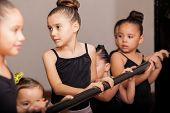 stock photo of ballet barre  - Cute little ballet dancers standing next to a ballet barre and paying attention to their teacher - JPG