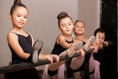 foto of leotard  - Cute little girl loving her ballet class and raising her leg on a ballet barre - JPG