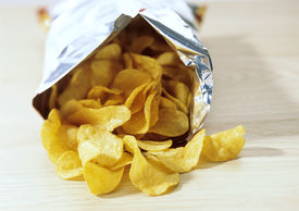 stock photo of potato chips  - Bag of potato crisps snacks chips junk food - JPG