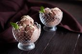 stock photo of chocolate spoon  - Two portions of delicious chocolate ice cream with almonds and mint leaf in crystal bowls and dark brown cloth on a wooden board appetizing dessert food closeup - JPG