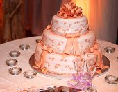 Three tiered wedding cake and champagne glasses on a table