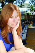 Mature woman looking sad and depressed sitting alone on a park bench
