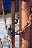 foto of chain link fence  - Old rusty lock on a rusty chain link security fence closeup view - JPG