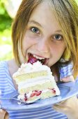 Teenage girl eating a piece of strawberry cake