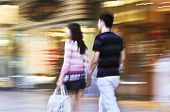Couple shopping in a mall, panning shot, intentional in-camera motion blur