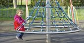 Young child having fun on a roundabout.