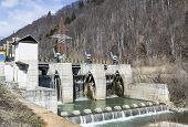 foto of hydro-electric  - Small hydro electric dam harnessing water power in a mountain area - JPG