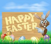 pic of wooden basket  - Happy Easter sign with Easter bunny pointing at the wooden sign with the message Happy Easter written on it - JPG