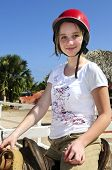 Young girl in a saddle wearing red helmet