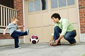 picture of bounce house  - Father teaching son to play soccer on driveway - JPG