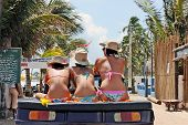 Three women with different heights wearing bikinis and hats, sitting on a buggy.