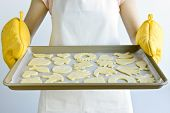 Woman holding a cookie tray with homemade cookies for baking