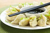 Closeup on plate of steamed dumplings with soy sauce and chopsticks
