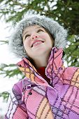 Portrait of happy teenage girl in winter ski jacket looking up