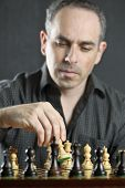 Man moving a chess pawn on wooden chessboard as first move