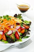 Plate of healthy green garden salad with fresh vegetables served with balsamic dressing