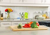 Modern kitchen interior with fresh vegetables on natural stone countertop
