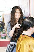 Happy hairdresser cutting hair in her salon