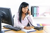 Serious young black business woman on phone taking notes in office