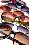 foto of protective eyewear  - Assorted styles of tinted sunglasses on white background close up - JPG