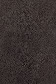 Dark brown natural leather background or texture close up