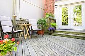Wooden deck on house with chairs and french doors