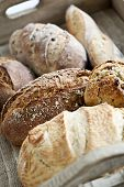 pic of baguette  - Various kinds of fresh baked bread loaves in wooden tray - JPG