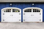 Two white garage doors with windows on blue house