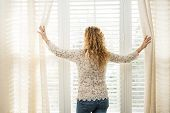 foto of lace-curtain  - Woman looking out big bright window with curtains and blinds - JPG