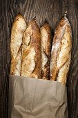 stock photo of baguette  - Four baguette bread loaves in paper bag on wooden background - JPG