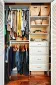 stock photo of apparel  - Clothes hung neatly in organized closet at home - JPG