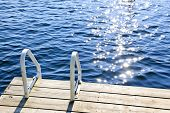 stock photo of dock a lake  - Dock and ladder on calm summer lake with sparkling water in Ontario Canada - JPG