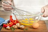 Closeup on man's hands whisking eggs in bowl for cooking omelet with vegetables