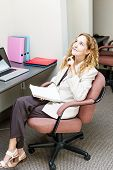 Businesswoman thinking of ideas in office workstation looking up